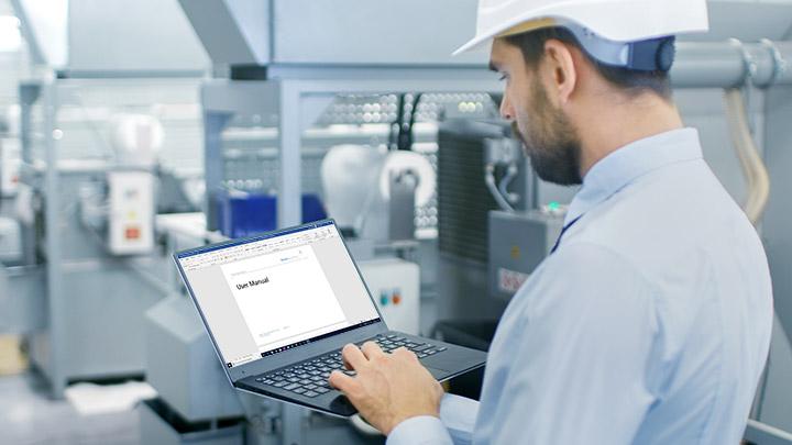 Mitarbeiter schreibt User Manual am Computer